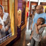 Visitors reflect on the photo of a black woman at the African American Museum in Philadelphia./PRNewswire
