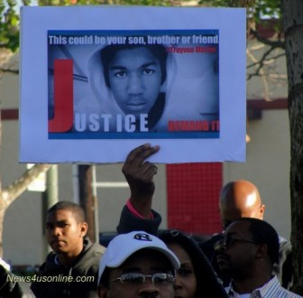 Protesting justice: A photo of slain teenager Trayvon Martin is held at a rally in Los Angeles. Photo: Dennis J. Freeman