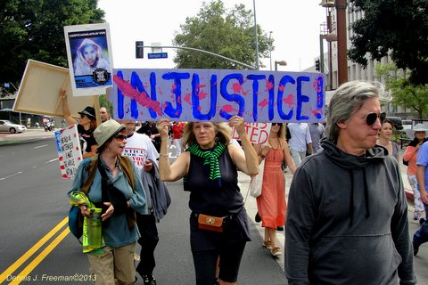 Demonstrators walk through downtown Los Angeles calling on the federal government to bring charges against George Zimmerman. Photo: Dennis J. Freeman
