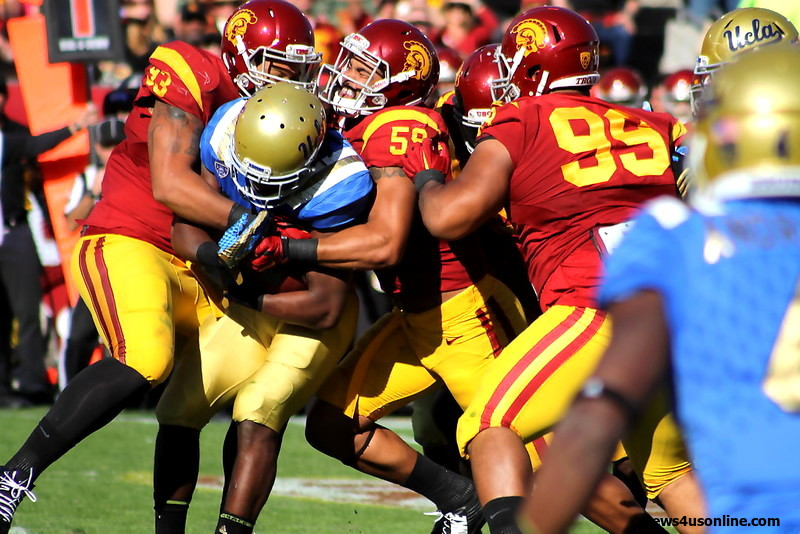 USC defenders swarm over UCLA running back Paul Perkins. Photo by Dennis J. Freeman/News4usonline.com