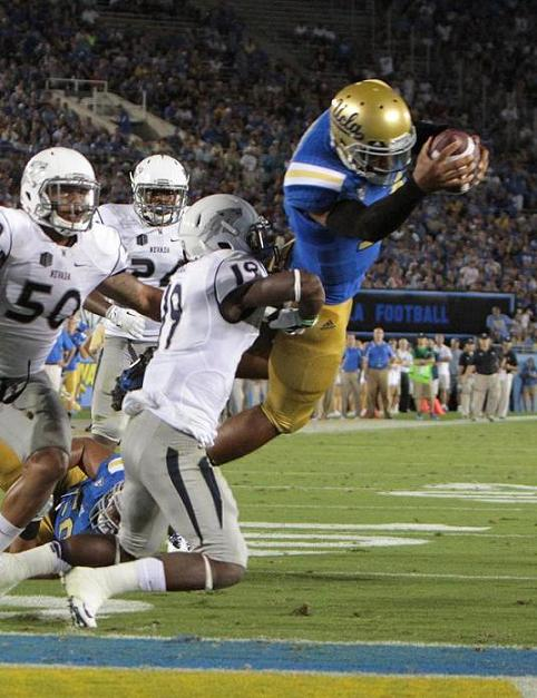 Over the top: Brett Hundley shows off his airborne skills against Nevada. Photo Credit: Jevone Moore/Full Image 360