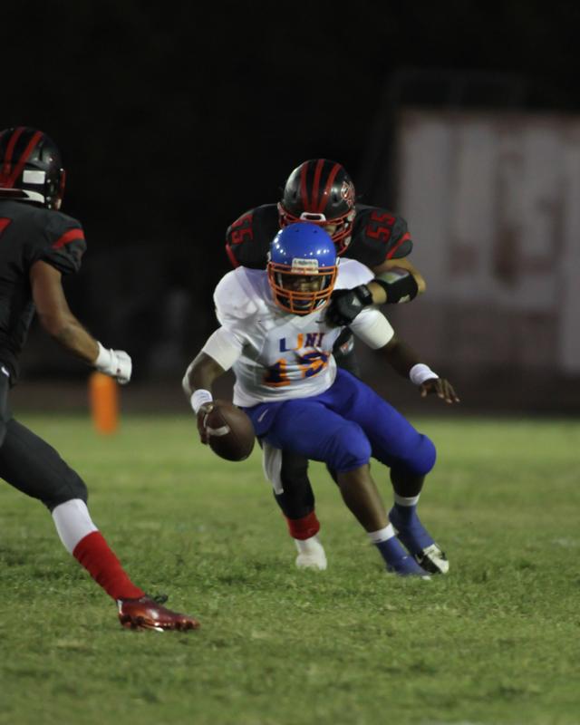 University Quarterback Paul Davis (15) was under fire all night from the Rams. Photo Credit: Jevone Moore Courtesy of Full Image 360 / News4usonline.com