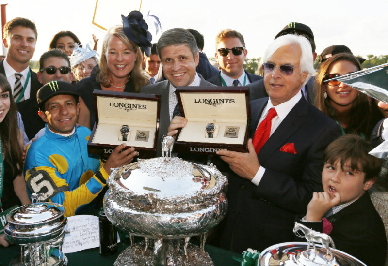 Jennifer Judkins and Juan Carlos Capelli, center, both of Longines, award Jockey Victor Espinoza, left, and Bob Baffert, right, Longines Conquest Classic 18K gold timepieces after Espinoza rode American Pharaoh to win the first Triple Crown in 37 years at the 147th Belmont Stakes at Belmont Park Race Track, Saturday, June 6, 2015 in Elmont, N.Y. (Photo by Stuart Ramson/Invision for Longines/AP Images)