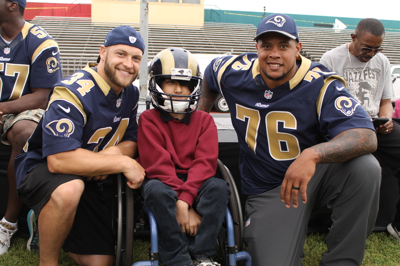 Rams players (left to right) Chase Reynolds (34) and Rodger Saffold (76) bring a smile to a young fan during the Rams Play 60 Field Day event in Inglewood, California. Photo by Dennis J. Freeman/News4usonline.com