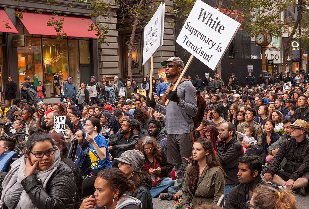 """Marchers sit on Market Street in Union Square, San Francisco, during a rally against police violence. One person standing holds signs reading """"Say It Loud, I'm Black & Proud!"""" and """"White Supremacy Is Terrorism!""""Photo Credit: Pax Ahimsa Gethen/Wikipedia Commons"""