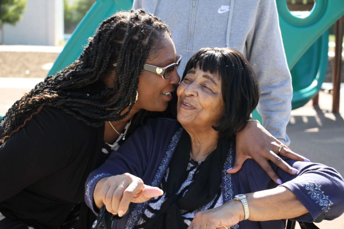 Dr. Christina Rogers, sister of Latasha Harlins, plants a kiss on Ruth Harlins. The two women attended a ceremony that renamed a playground in honor of Latasha Harlins. Photo credit: Dennis J. Freeman/News4usonline
